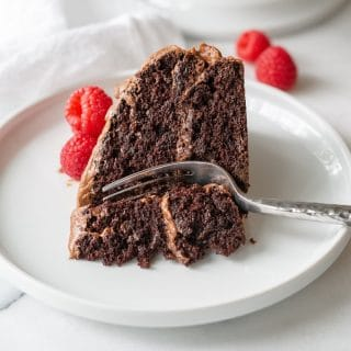a close up of a slice of gluten free chocolate cake on a white plate with a fork and raspberries