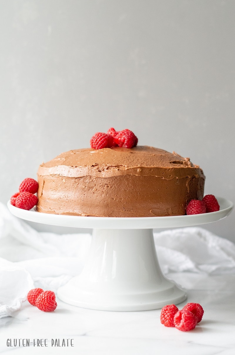 a straight on view of a chocolate cake topped with chocolate frosting and raspberries on a white cake stand