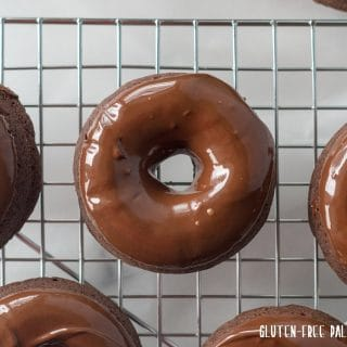 close up of some Gluten-Free Vegan Chocolate Espresso Donuts on a wire cooling rack.
