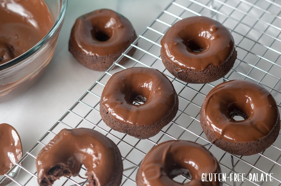 gluten free vegan chocolate donuts on a wire cooling rack topped with melted chocolate