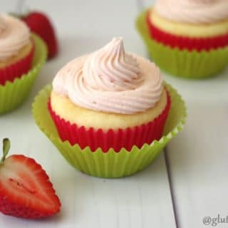 a close up of a gluten free strawberry lemonade cupcake topped with pink frosting baked in a red paper liner, in a green paper liner