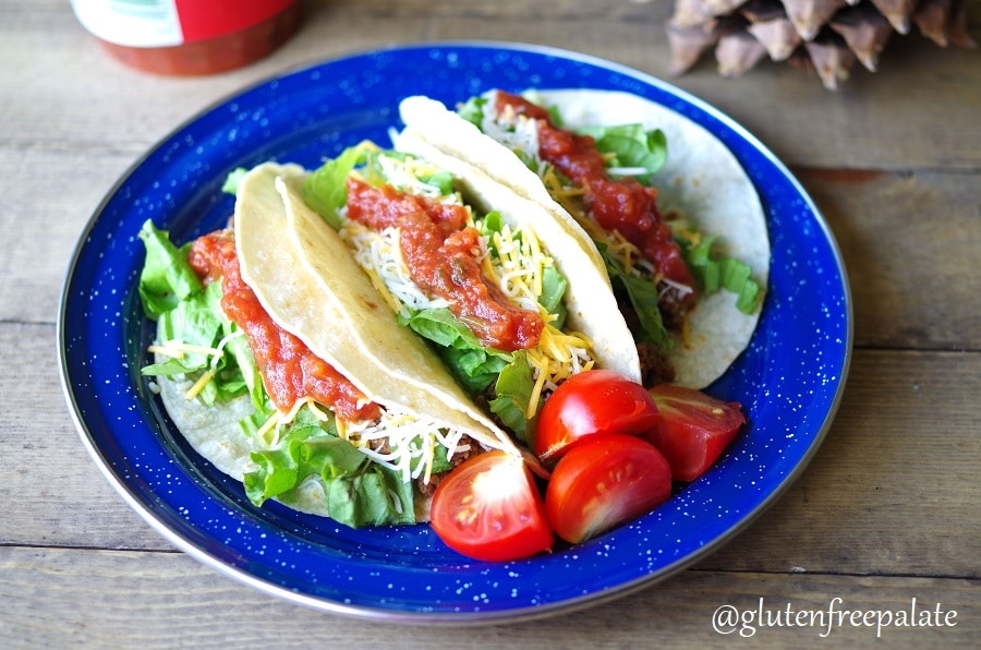 three tacos on a blue plate with sliced tomotoes