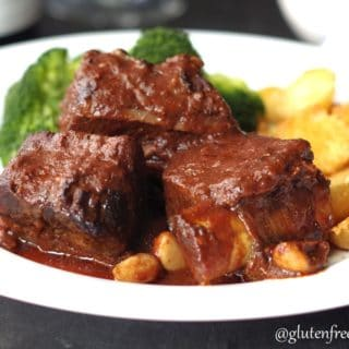 a close up of beef short ribs on a white plate with a side of broccoli and potatoes