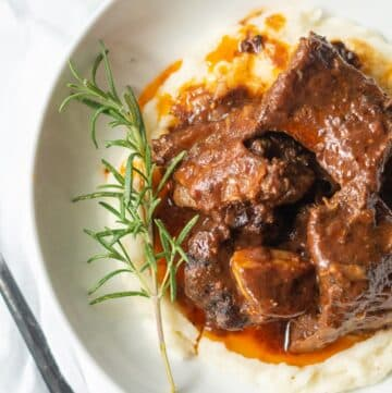 close up top down view of beef short ribs over mashed potatoes