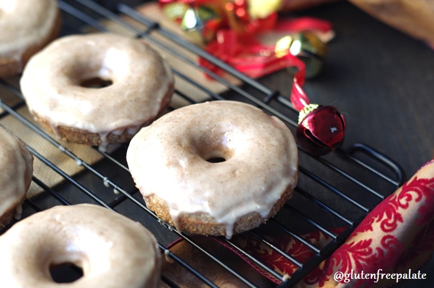 a side view of gluten free chai donuts on a wire rack next to a red bell and a holiday ribbon