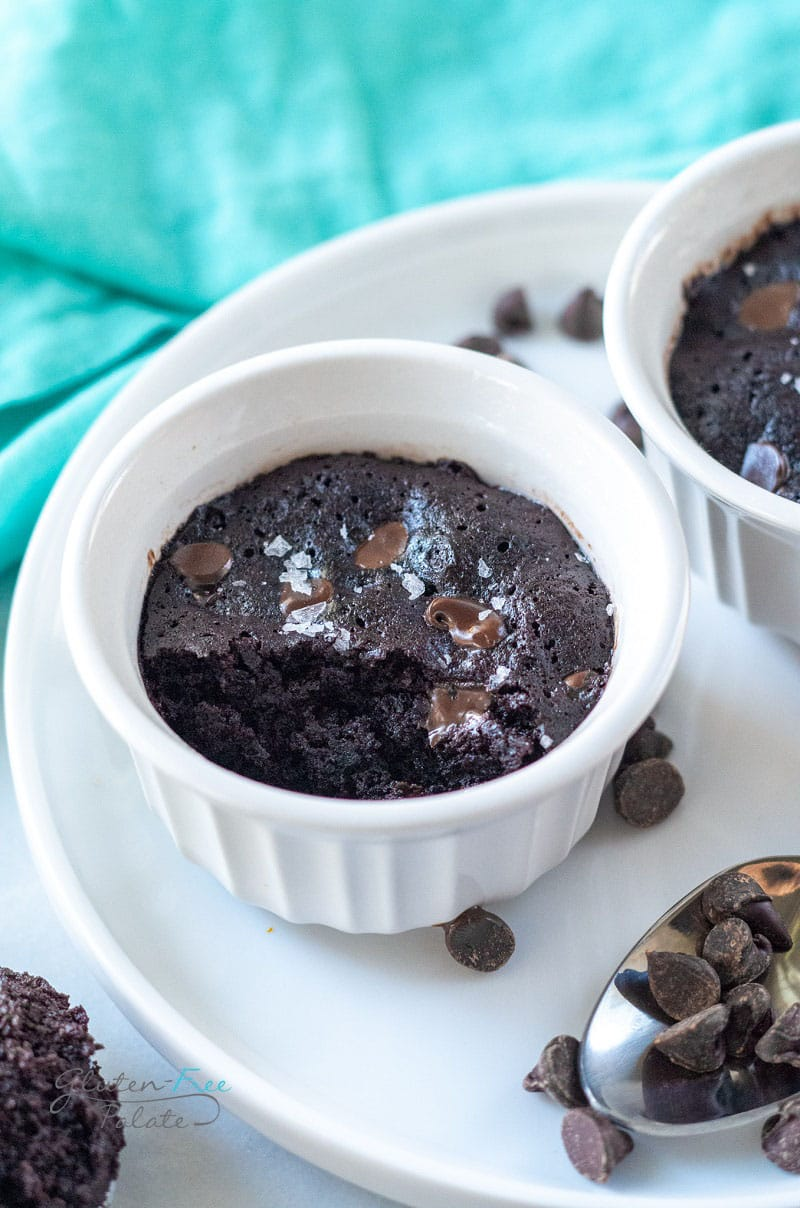 angled view of a vegan mug brownie in a ramekin with a bite out