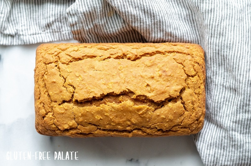 A loaf of gluten-free pumpkin bread on a white counter with a stripe towel next to it