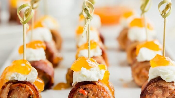 Close up view of sausage appetizers topped with goat cheese
