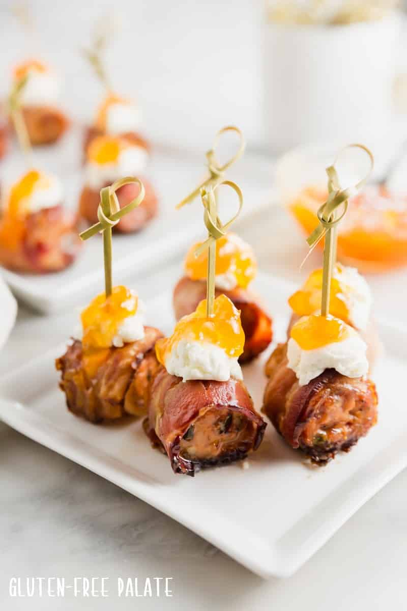 five sausage appetizers on a white plate