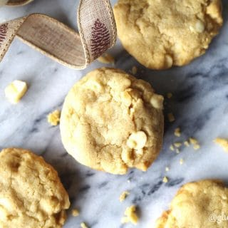 a close up of four gluten-free white chocolate macadamia cookies on a marble slab with a browni ribbon