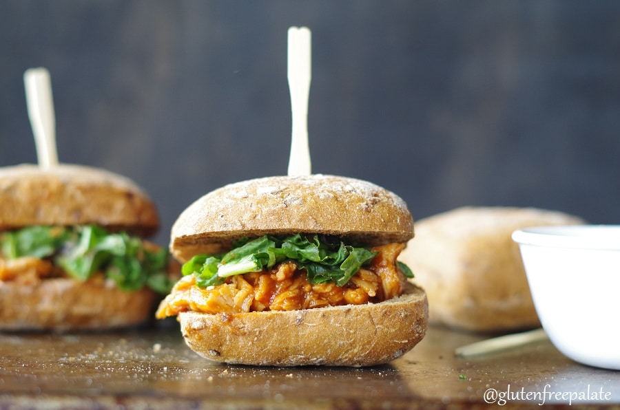 Shredded gluten-free chicken on a bun with sauce and lettuce, with a tooth pick in the center