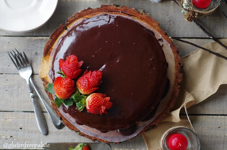 a top down view of a Gluten-Free Vegan Chocolate Ganache Cake topped with strawberry roses, served on a wood cake platter
