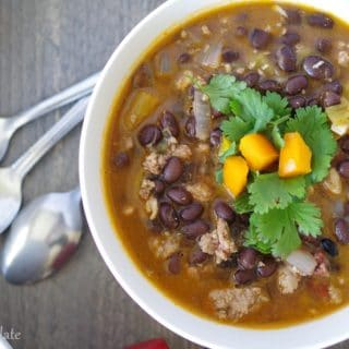 A close up top view of spicy black bean soup topped with cilantro