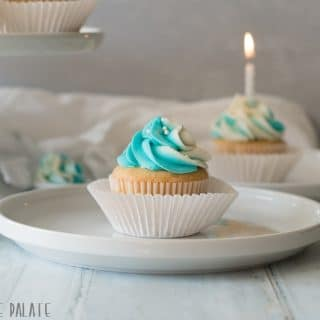 a close up of a gluten free vanilla cupcake topped with blue and white swirled frosting, on a white plate