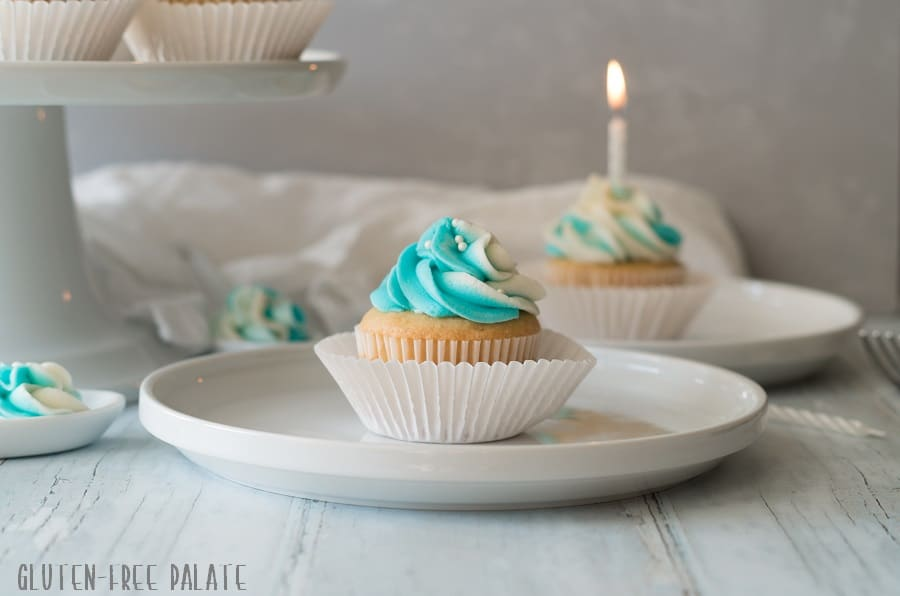 a gluten free vanilla cupcake topped with blue and white swirled frosting, on a white plate in front of another cupcake