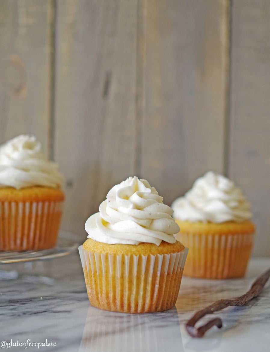 three vanilla bean cupcakes with vanilla frosting on a marble counter