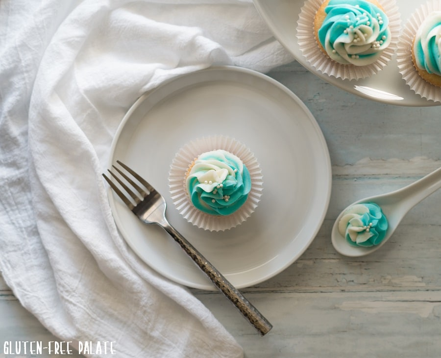 top down view of a gluten free vanilla cupcake topped with blue and white swirled frosting, on a white plate with a fork