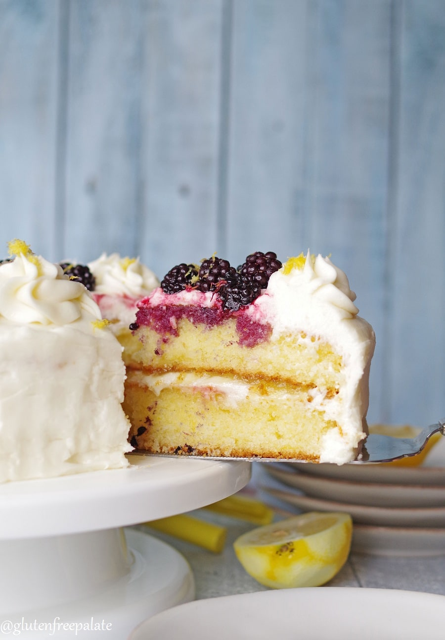 serving knife with a slice of lemon cake on it on a white cake plate with lemon and blackberries
