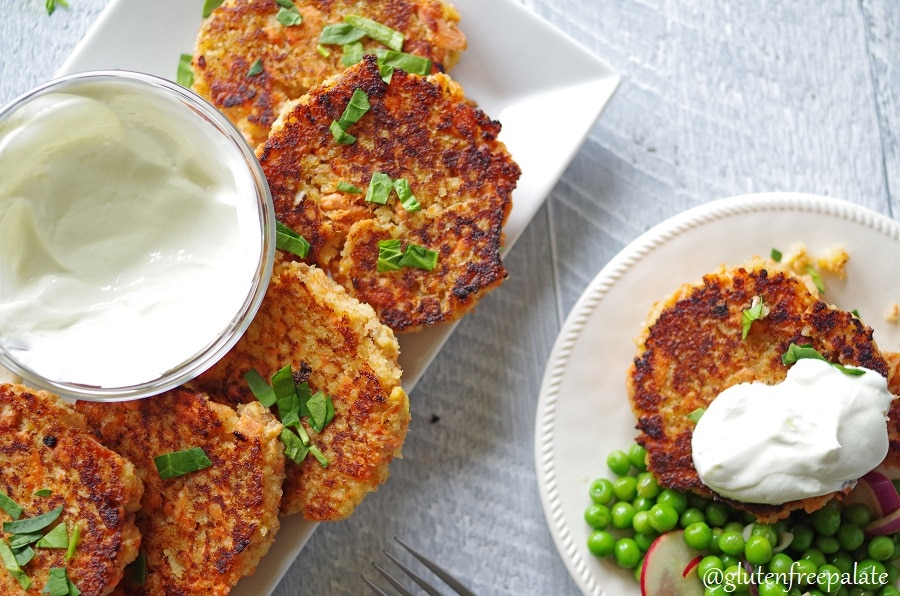 Gluten-Free Salmon Cakes on a white plate with green garnish, and a bowl of white sauce, next to a plate of salmon cakes and peas