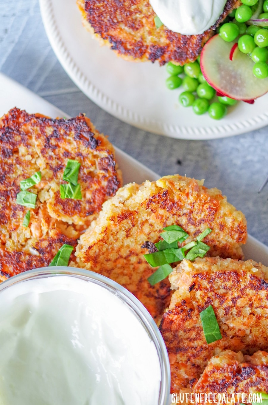 Gluten-Free Salmon Cakes on a white plate with green garnish next to a plate of salmon cakes and peas
