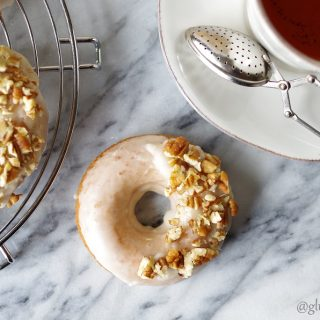 a top down view of a maple donut with white glaze and chopped nuts