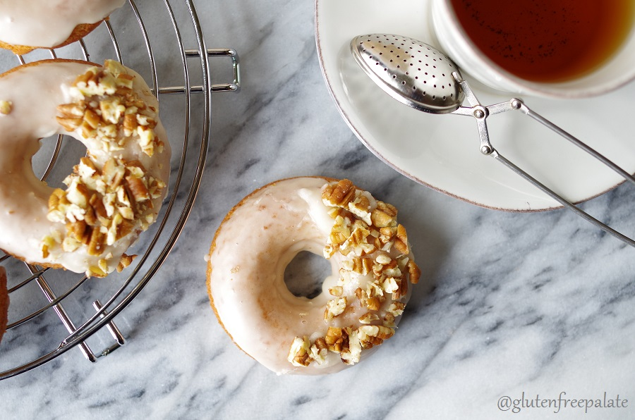 a top down view of a maple donut with white glaze and chopped nuts next to a donut on a cooling rack and a cup of tea