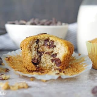 a paleo chocolate chip muffin with a bite out showing the chocolate chips inside