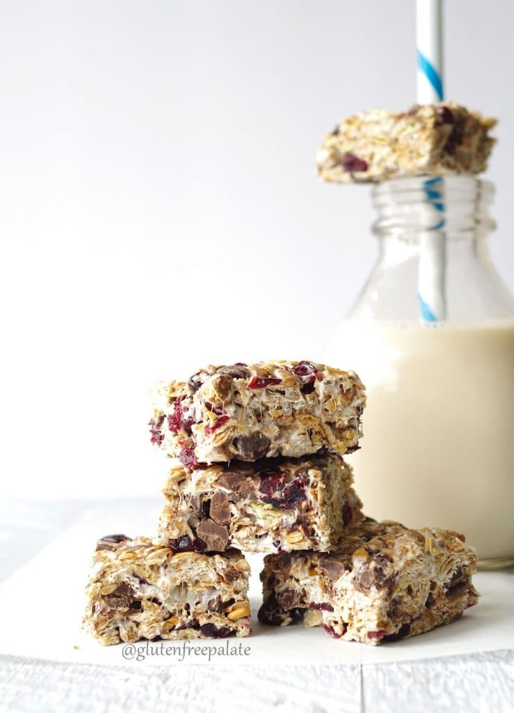 four bliss bars stacked on a piece of parchment paper with a jar of milk and a bar in the background