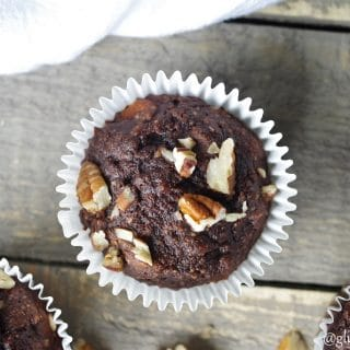 a close up of a top down view of a chocolate banana muffin topped with chopped nuts