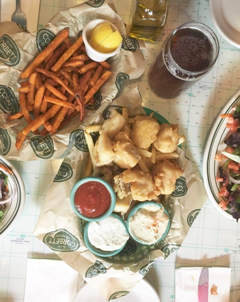 a basket of friend fish with dipping sauces next to a basket of sweet potato fries