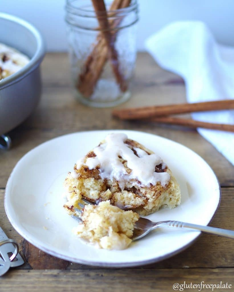 a side view of a slice of cinnamon roll cake on a white plate with a fork