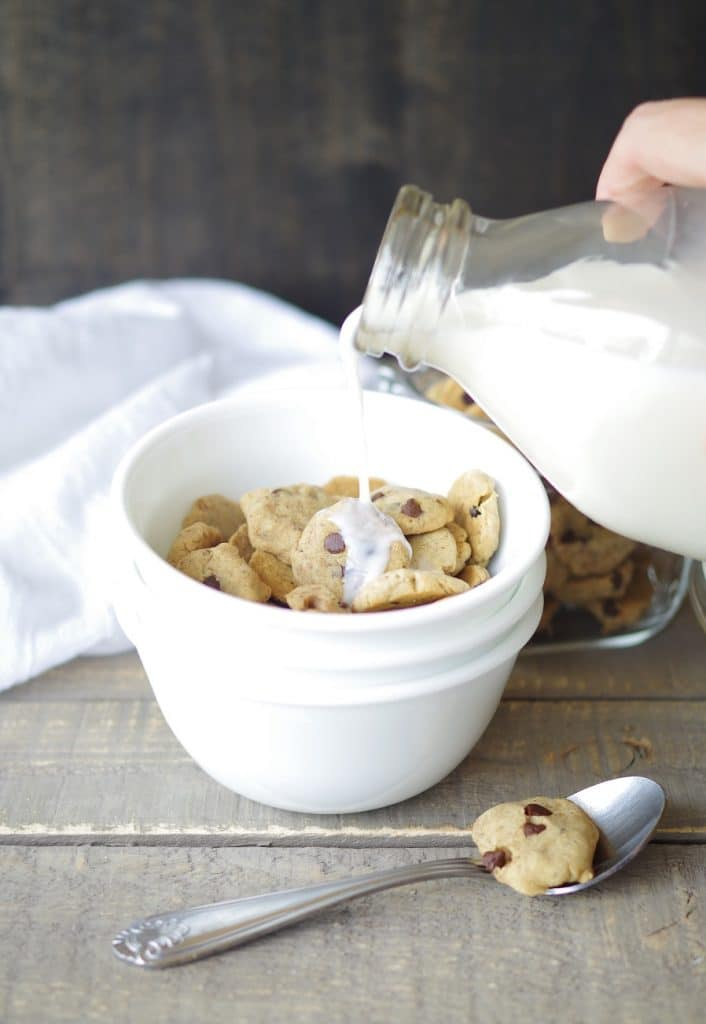 milk being poured over gluten free vegan cereal in the shape of chocolate chips cookies in a white bowl