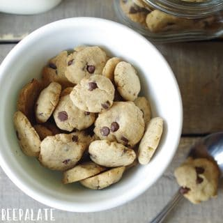 a close up of gluten free vegan cereal in the shape of chocolate chips cookies in a white bowl