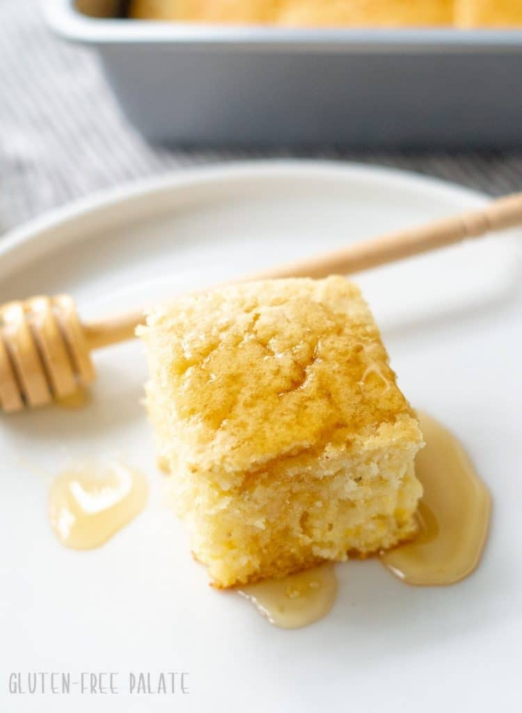 A slice of gluten-free cornbread on a white place with a honey drizzle.