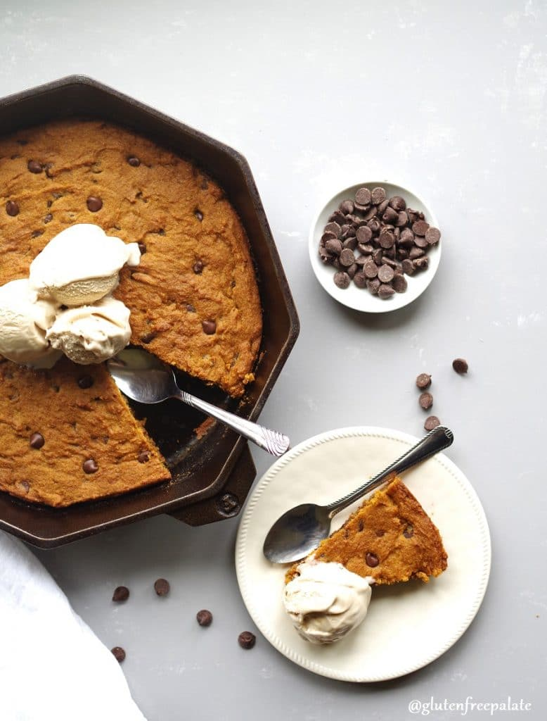 gluten free pumpkin chocolate chip skillet cookie in a cast iron skillet topped with ice cream next to a piece of cookie on a white plate