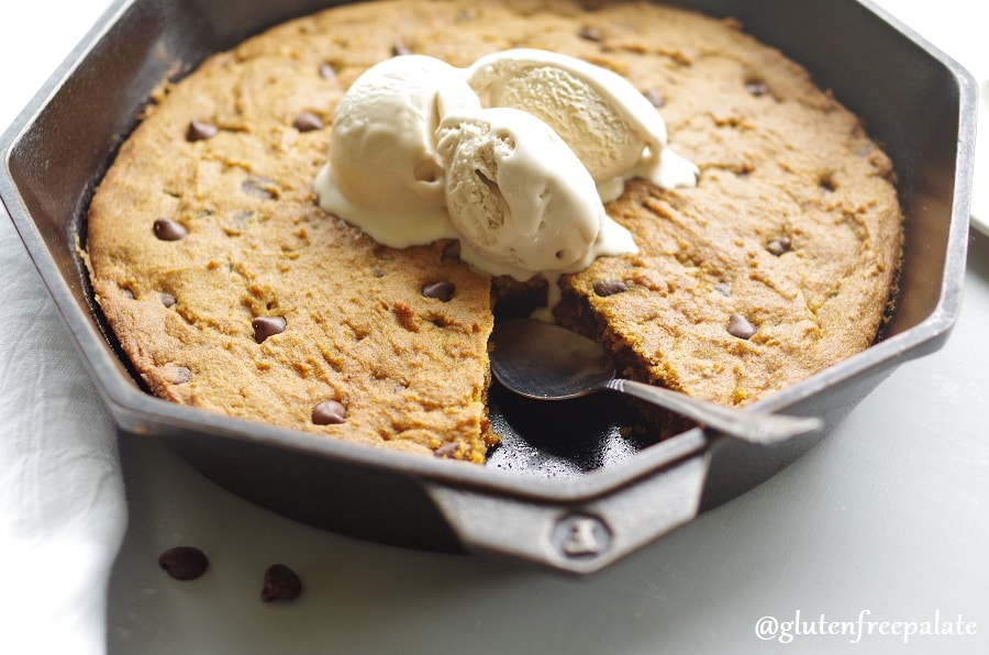 a side view of gluten free pumpkin chocolate chip skillet cookie in a cast iron skillet topped with three scoops of vanilla ice cream
