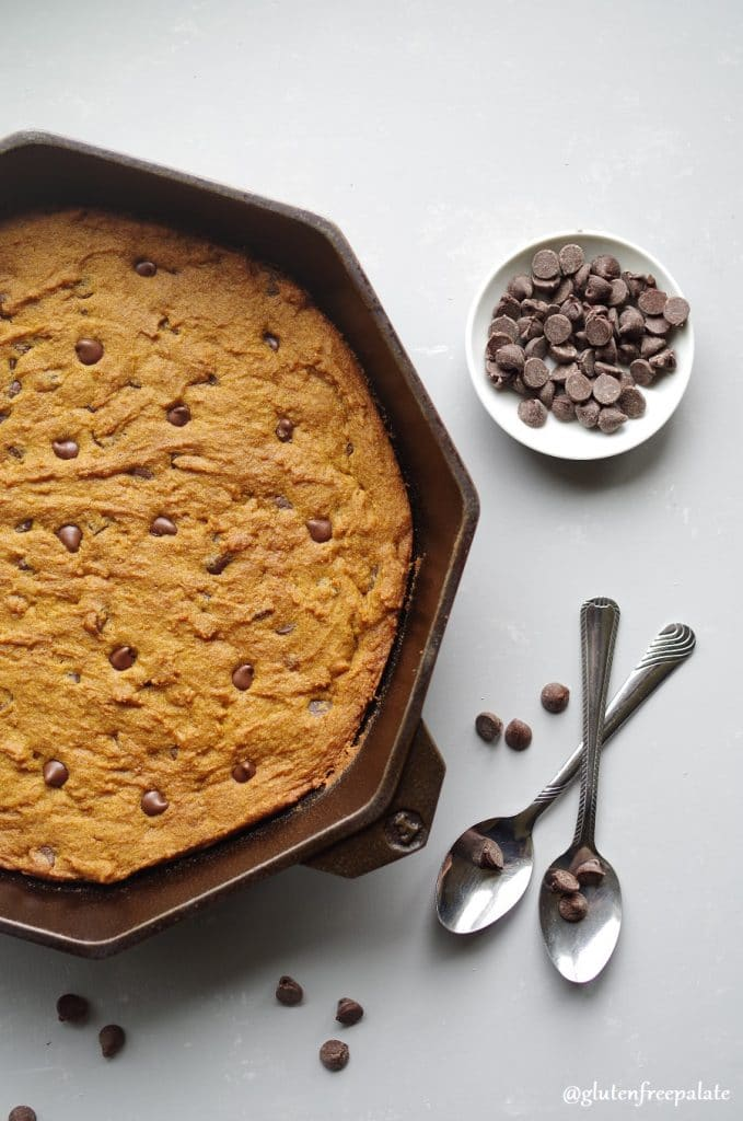 gluten free pumpkin chocolate chip skillet cookie in a cast iron skillet next to two spoons and a bowl of chocolate chips