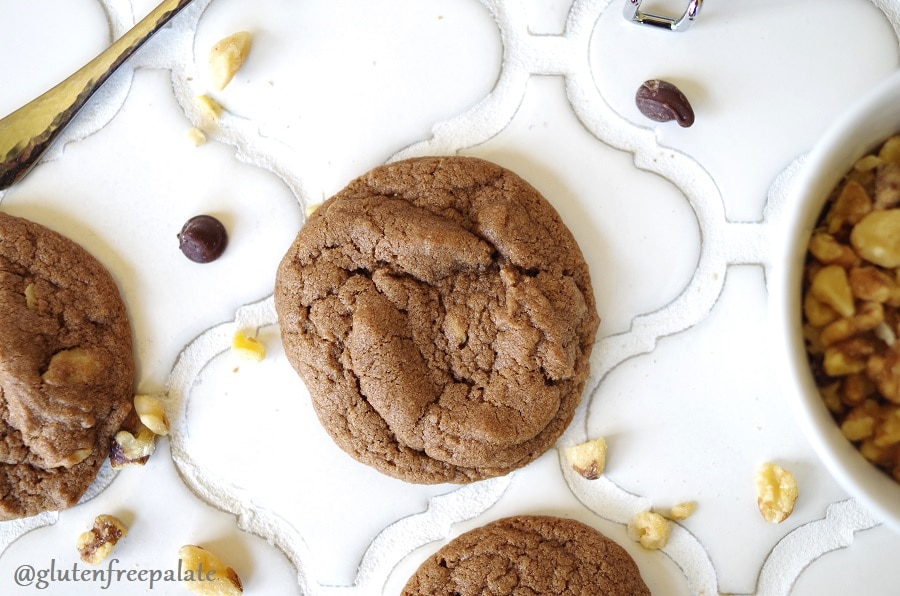 top view of Gluten-Free Chocolate Drop Cookies on a white tile backdrop with scattered chocolate chips and chopped nuts