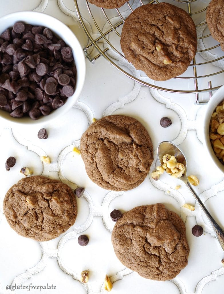 Gluten-Free Chocolate Drop Cookies on a white counter next to a bowl of chocolate chips and a spoon with nuts