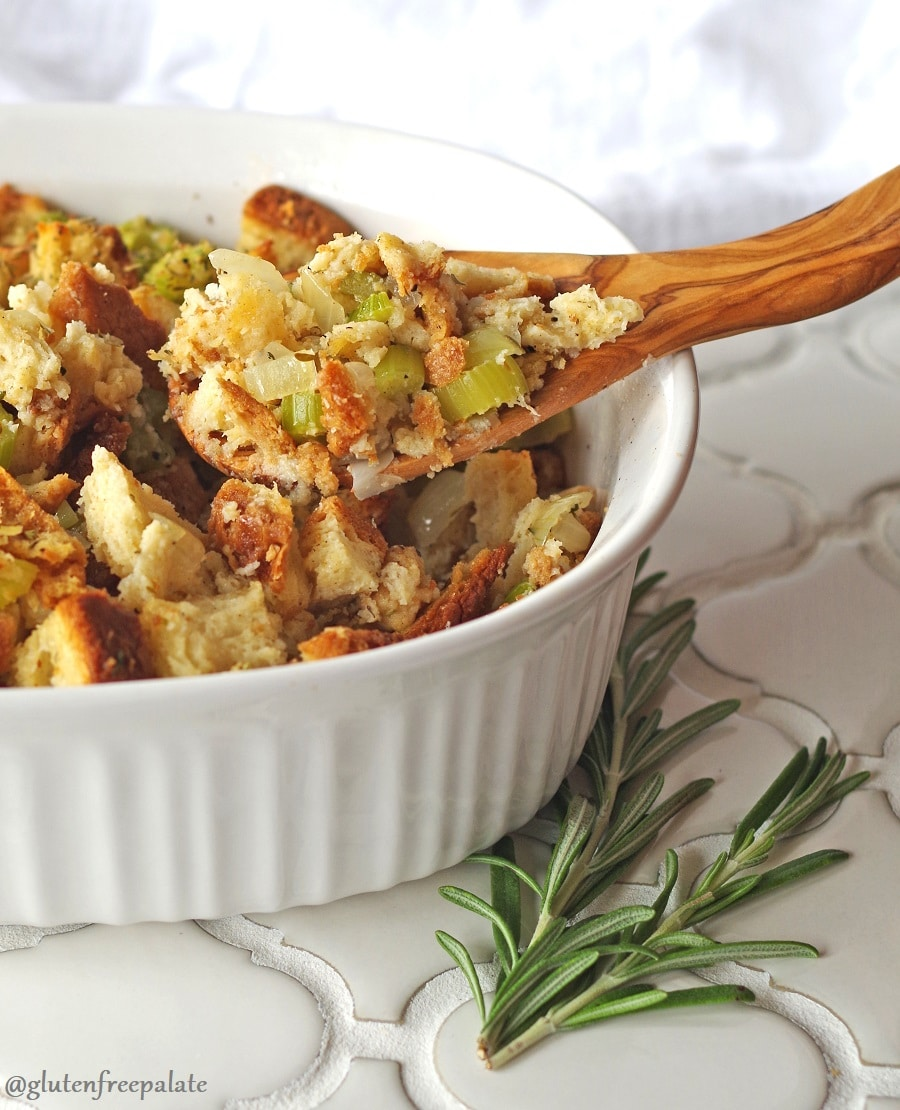 gluten free stuffing in a white ceramic dish with a wooden spoon and a spring of rosemary