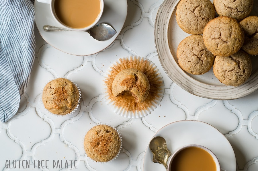 paleo snickerdoodle muffins on a white counter next to a cup of coffee and a plate of muffins