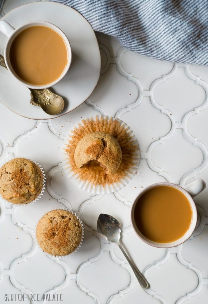 a top down view of paleo snickerdoodle muffins on a white counter next to two cups of coffee