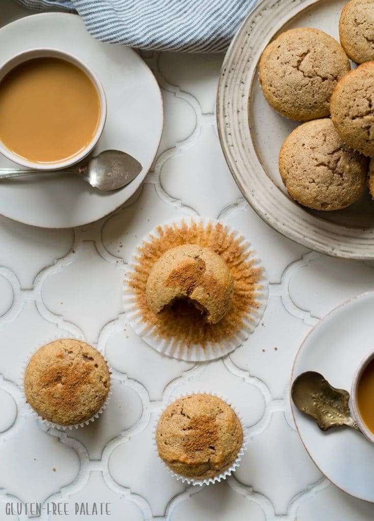 a top down view of paleo snickerdoodle muffins on a white counter next to a cup of coffee and a plate of muffins
