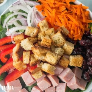 close up of top down view of a salad topped with croutons and veggies