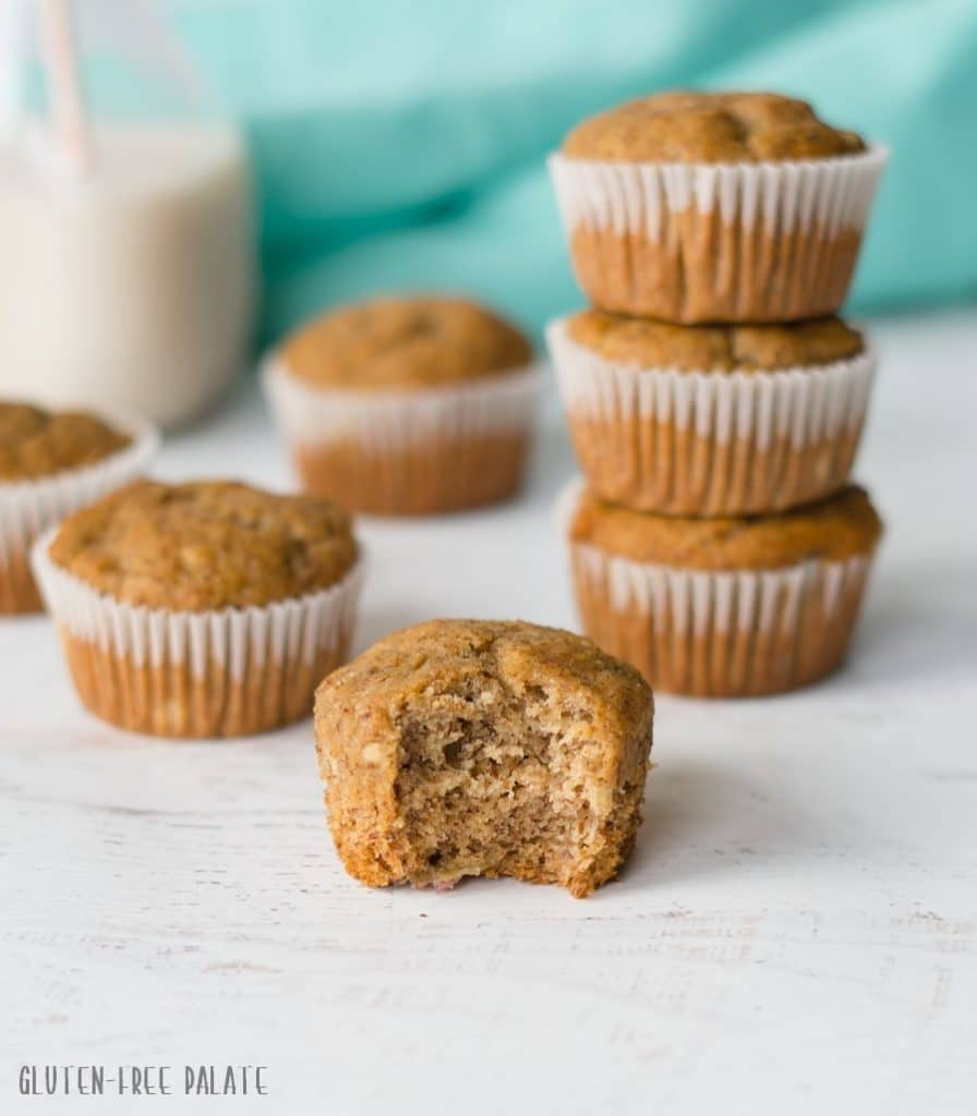 a muffin with a bite out in front of three stracked muffins and another muffin