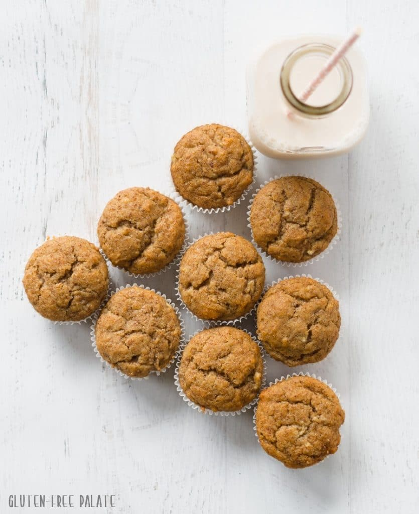 Gluten free honey flaxseed muffins arranged next to a jar of milk with a straw