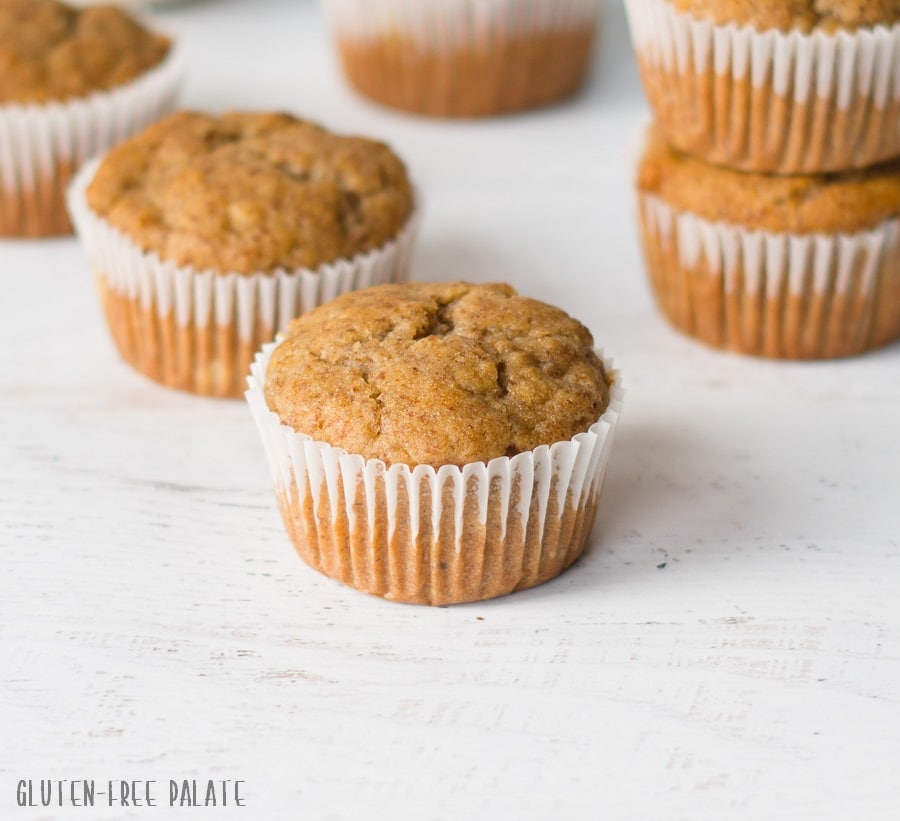 a flaxseed muffin in a white paper liner next to other muffins