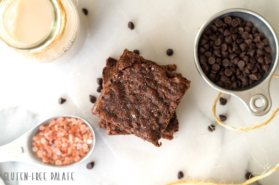 a top down view of three brownies stacked on top of eachother next to a jar of milk and a cup of mini chocolate chips