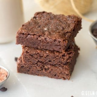 a close up of three brownies stacked on top of eachother with a jar of milk in the background