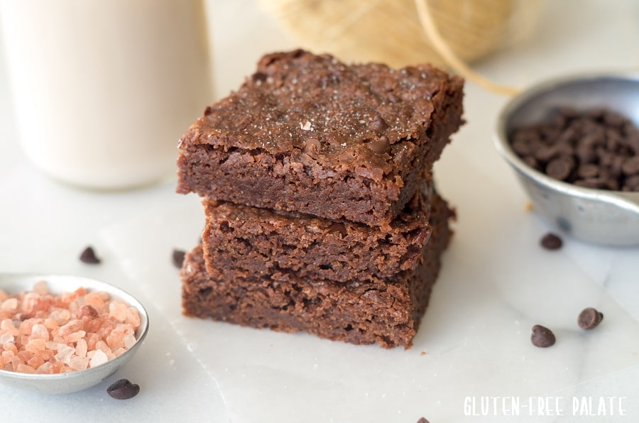 a close up of three brownies stacked on top of eachother next to a bowl of salt and a cup of chocolate chips